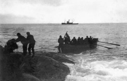 """Fotografía tomada por el fotógrafo y tripulante de la expedición a bordo del """"Endurance"""", Frank Hurley. Los náufragos en el momento del rescate, al fondo la """"Yelcho"""", comandada por el Piloto Pardo."""
