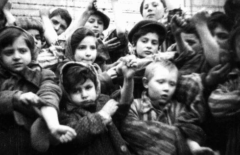 Algunos de los 600 niños supervivientes del campo de concentración de Auschwitz muestran los números de identificación tatuados en sus brazos.